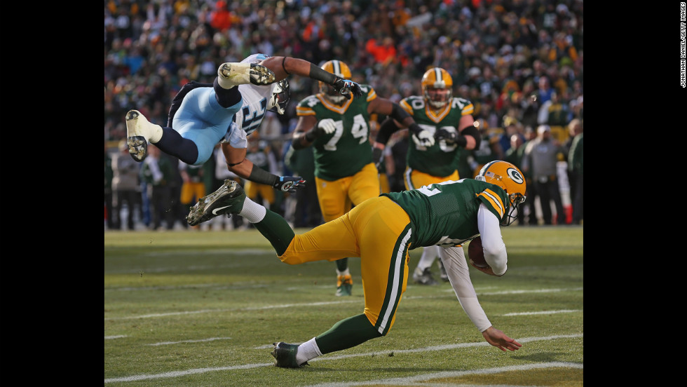 Aaron Rodgers of the Packers rolls into the end zone after being grazed by Al Afalava of the Titans on Sunday.