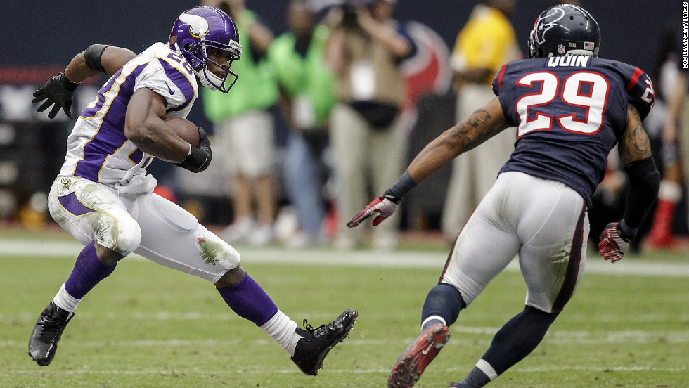 Adrian Peterson of the Minnesota Vikings looks to avoid a tackle by Glover Quin of the Houston Texans at Reliant Stadium on Sunday in Houston.