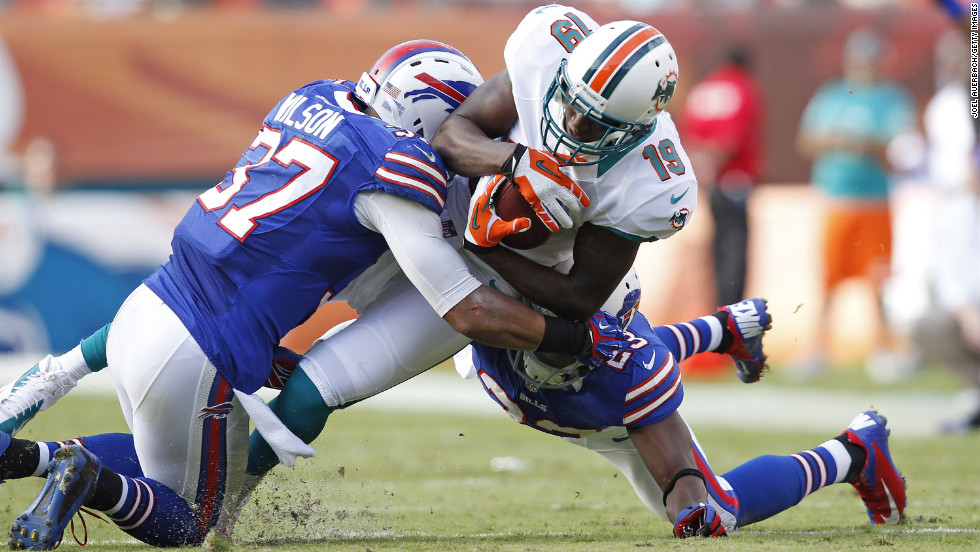 Armon Binns of the Miami Dolphins is tackled by Aaron Williams and George Wilson of the Buffalo Bills as he runs with the ball on Sunday at Sun Life Stadium in Miami Gardens, Florida. The Dolphins defeated the Bills 24-10.