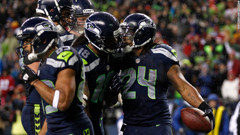 Marshawn Lynch, right, of the Seattle Seahawks celebrates with teammates after scoring a nine-yard touchdown catch on Sunday.