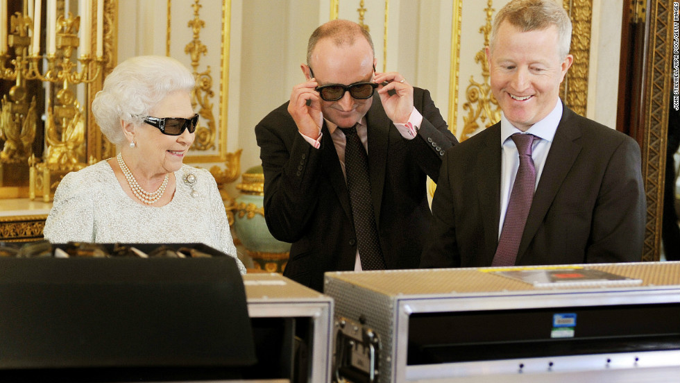 Queen Elizabeth II watches the recording of her Christmas message with producer John McAndrew and director John Bennett (R). The speech will be broadcast to the Commonwealth in 3D for the first time in the White Drawing Room of Buckingham Palace.