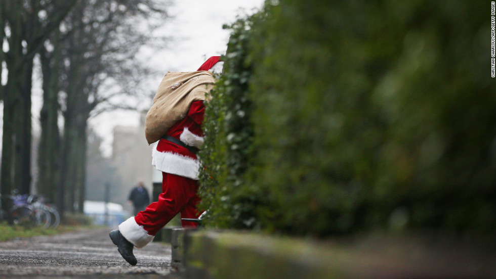 "A man decked out as Santa Claus slips through the back streets of Hamburg, Germany, on Monday, December 24. <a href=""http://cnnphotos.blogs.cnn.com/2012/12/22/magnum-santas/"">Related photos: Magnum Santas</a>"