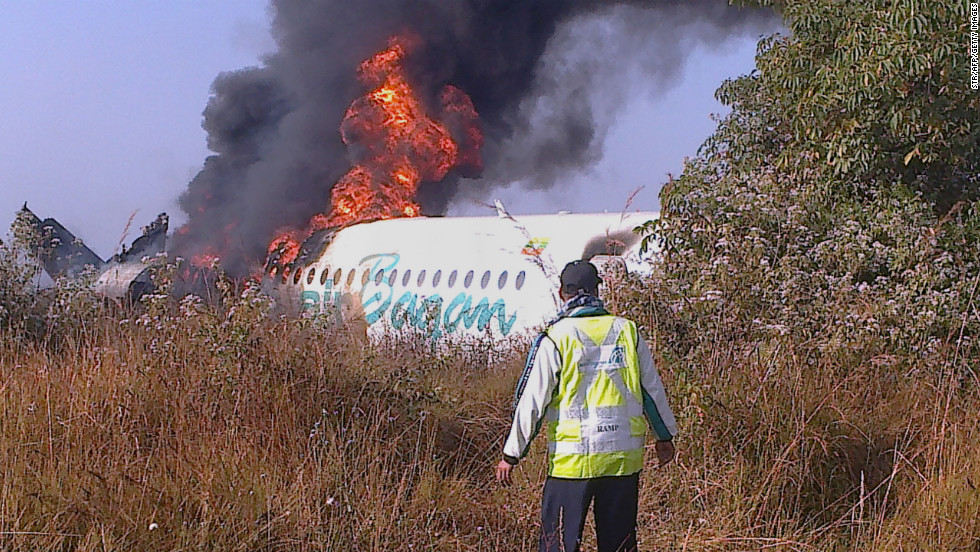 The Air Bagan plane, which was carrying 71 people, burns December 25 near Heho Airport. A tour guide on board the plane and a motorbike rider on the ground were killed.