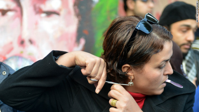 An Egyptian protester cuts her hair during a demonstration mostly by Egyptian women against their country's new constitution draft, on December 25, 2012 in Cairo.