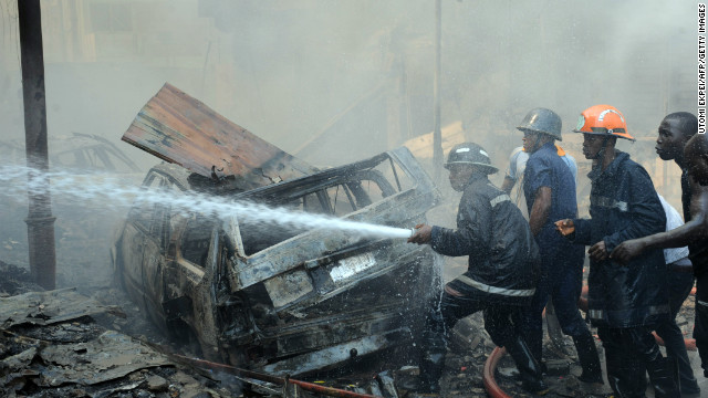 Firefigters try to put out a fire at the building following an explosion in Lagos on December 26, 2012.