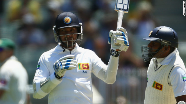 Kumar Sangakkara raises his bat after reaching 10,000 Tests in a record equaling feat.