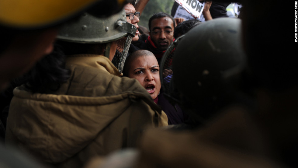 Demonstrators shout slogans and wave placards as they move toward India Gate in New Delhi on December 27.
