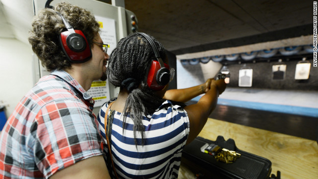 Domenic Lether teaches his girlfriend Ngozi Ogbeni how to shoot a Smith & Wesson .357 magnum revolver at a target range at the Los Angeles Gun Club.