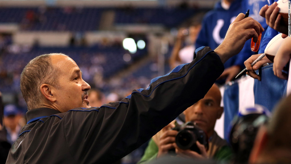 Head coach Chuck Pagano of the Indianapolis Colts signs autographs on Sunday.