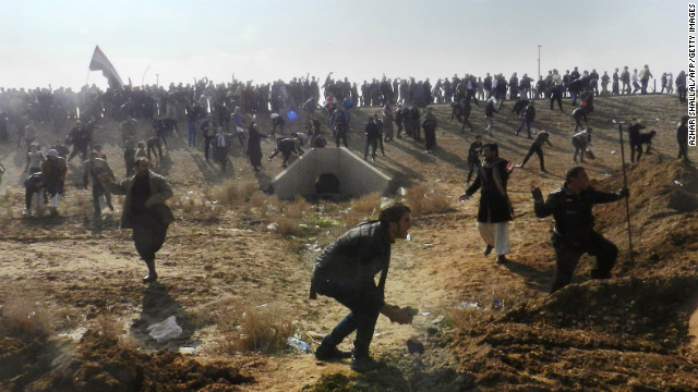 Iraqis throw stones after protesters attacked Iraq's deputy premier Saleh al-Mutlak on Sunday, December 30.