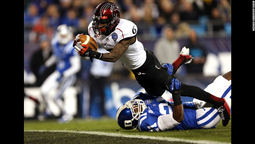 Anthony McClung of the Cincinnati Bearcats dives for a touchdown as Anthony Young-Wiseman of the Duke Blue Devils tries to bring him down on the goal line during the Belk Bowl at Bank of America Stadium on December 27 in Charlotte, North Carolina.