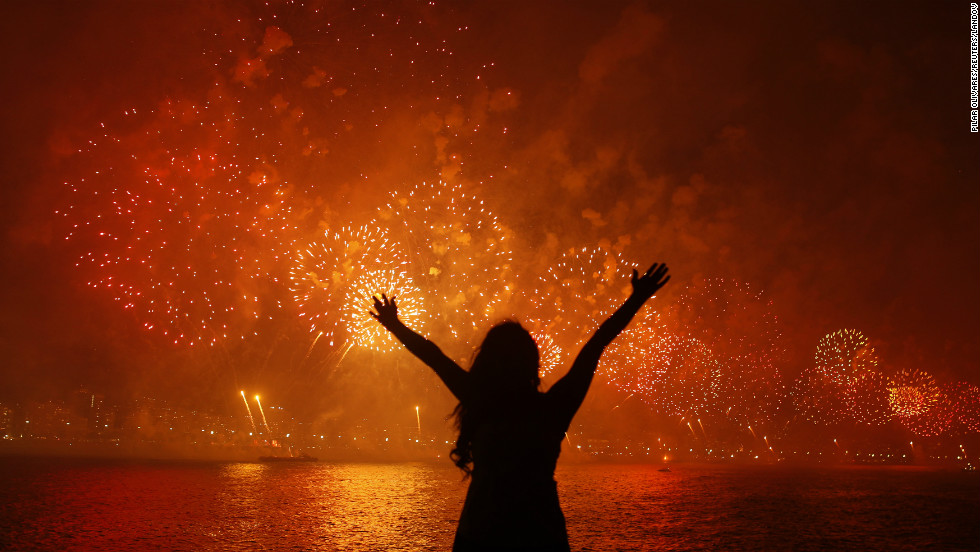 A woman watches fireworks burst above Copacabana Beach in Rio de Janeiro.