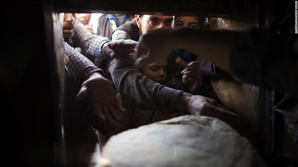 Syrians reach for bread at a bakery in Aleppo on Monday, December 31.