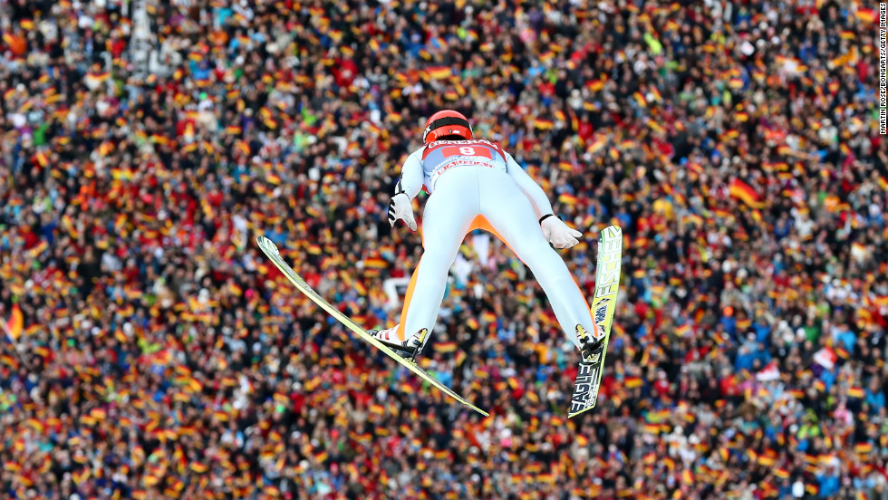Fans below wave German flags as countryman Andreas Wank competes during the final round on January 1.