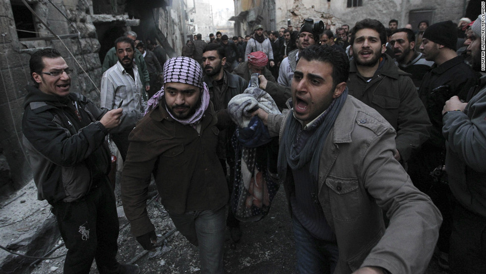 Syrians carry the body of a victim who activists said was killed during the bombing in the al-Ansari area of Aleppo, January 3.