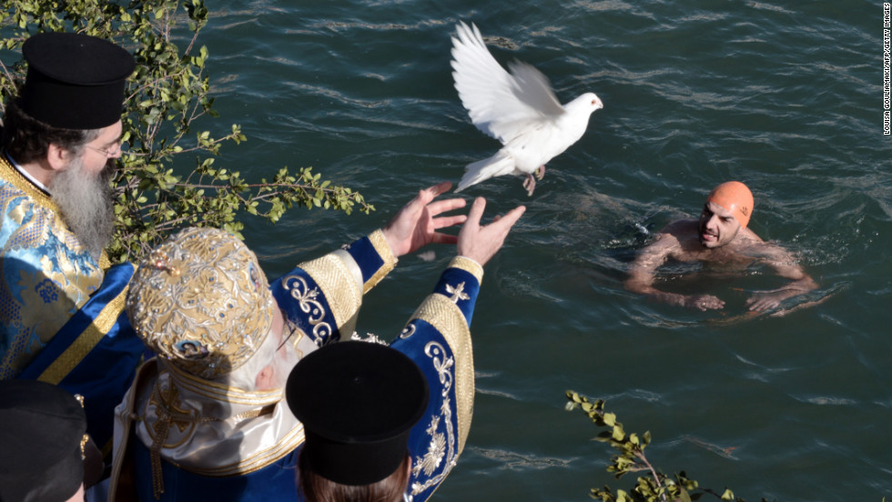 A priest releases a dove during the blessing of the waters during Epiphany celebrations in the city of Volos, Greece, on Sunday.