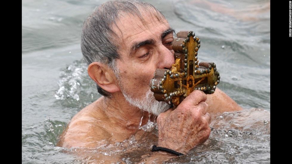A Greek Orthodox swimmer kisses the wooden cross he retrieved from the Golden Horn in Istanbul on Sunday.