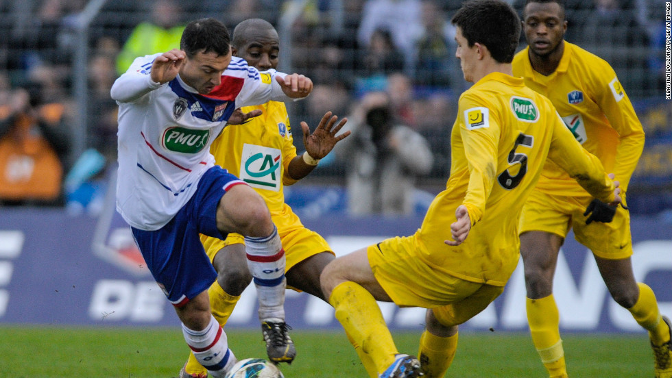 Lyon's French midfielder Steed Malbranque vies with Epinal's French defender Wilfried Rother as the home team get stuck into the top division side.