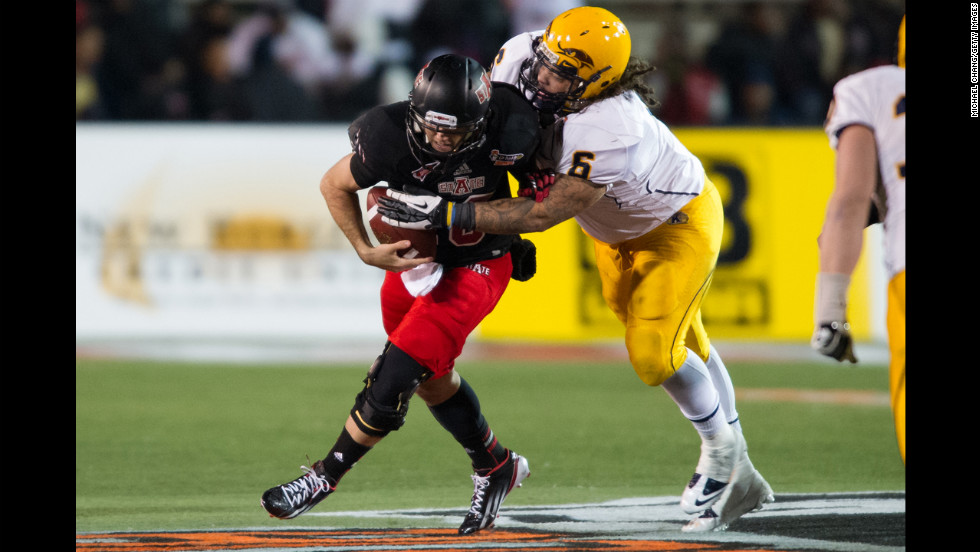 Arkansas State quarterback Ryan Aplin tries to elude a tackle by Kent State defensive lineman Dana Brown Jr. on January 6.