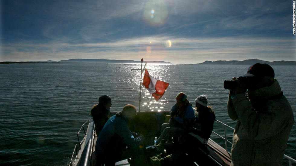 Tourists chatter and snap pictures aboard a boat on the Peruvian side of Lake Titicaca.