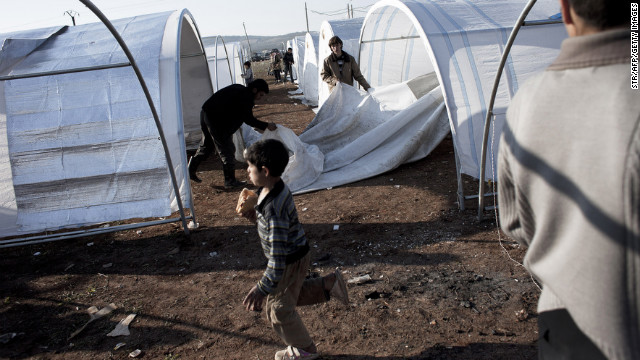 A Syrian family erects their tent at the Bab al-Salam refugee camp on the Syrian-Turkish border on January 1, 2013. Turkey, which supports the insurgency, is housing a total of some 150,000 Syrian refugees at camps near the border. AFP PHOTO / STR        (Photo credit should read -/AFP/Getty Images)