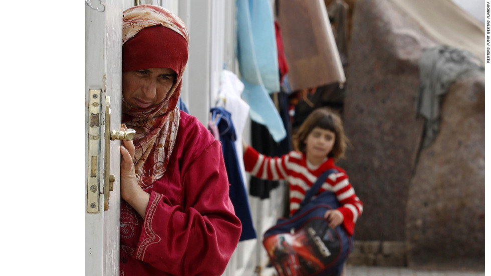 A woman stands at the entrance of her family's living area in a refugee camp named Container City on the Turkish-Syrian border, near Oncupinar in Turkey's Kilis province, on Monday, December 24.