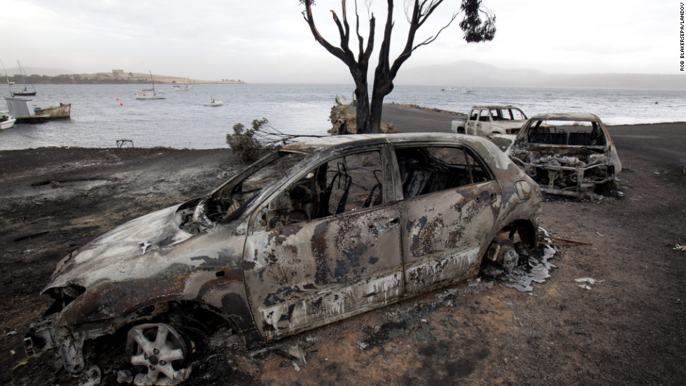 Burned out cars lie abandoned at the jetty on the Tasman Peninsula in Boomer Bay, Tasmania, on Tuesday.