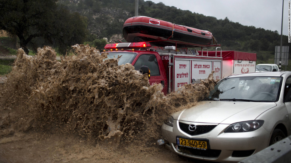 A fireman's truck drives through a flooded road to rescue people trapped in their vehicles near the Israeli-Arab town of Kfar Qara, in central Israel.