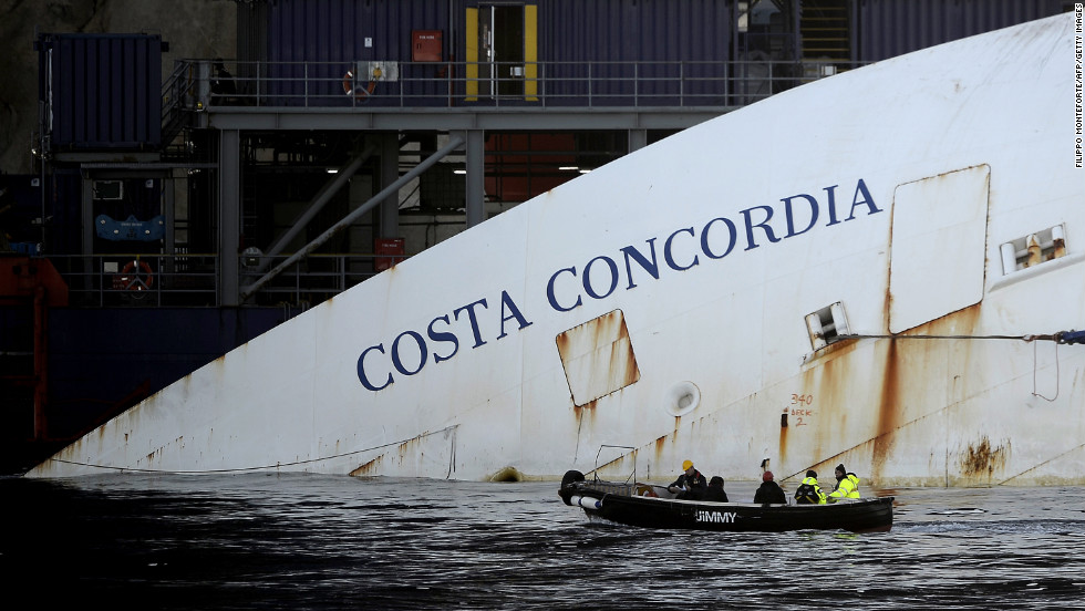 "Workers in a small boat pass by the Costa Concordia on Monday, January 7. <a href=""http://www.cnn.com/2012/01/14/europe/gallery/italy-ship/index.html"">See photos from the shipwreck in 2012.</a>"