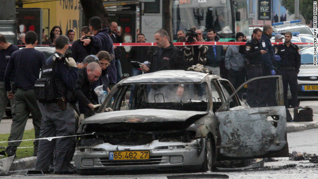 Investigators look at a damaged car after it exploded near the Israeli defence ministry in Tel Aviv on January 10, 2013.