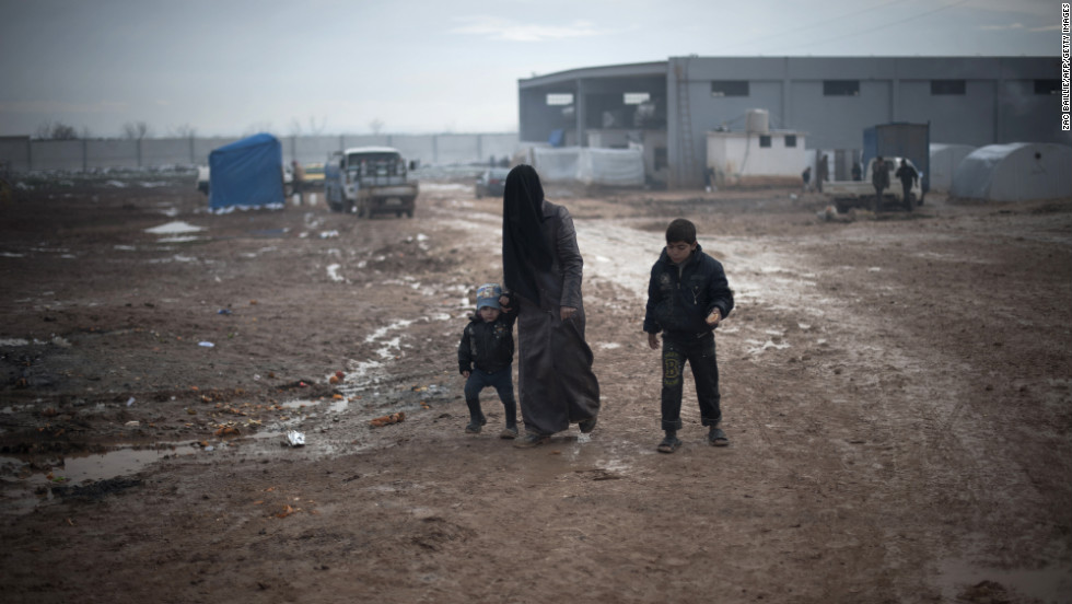 A Syrian mother and her two children walk through the mud after the first snow of the year fell the previous night at a refugee camp in Bab al-Salam on the Syria-Turkey border, on Wednesday, January 9.