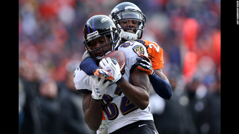 Ravens receiver Torrey Smith can't make the catch on a pass as he is wrapped up Denver's Champ Bailey.