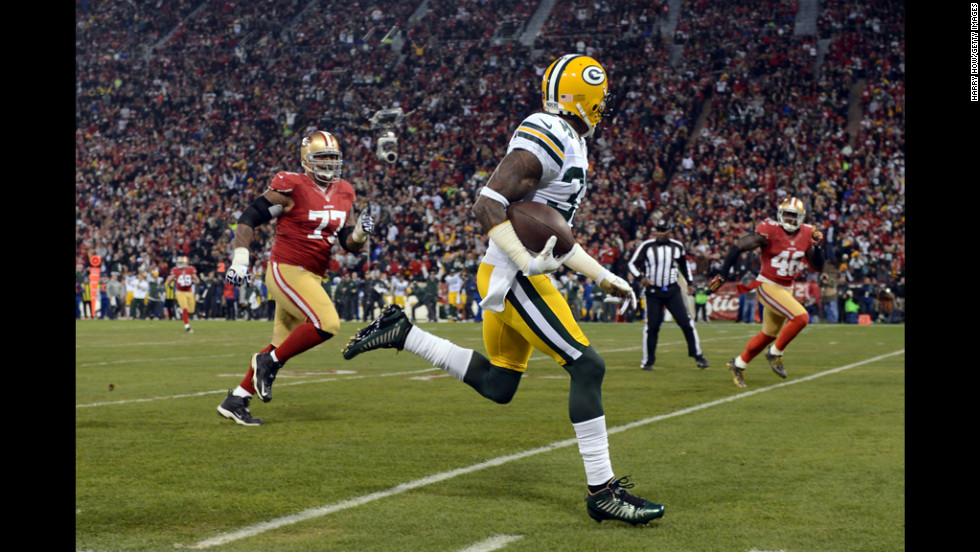 Cornerback Sam Shields of the Packers runs the ball back for touchdown after an interception against quarterback Colin Kaepernick of the 49ers in the first quarter of Saturday's playoff game.
