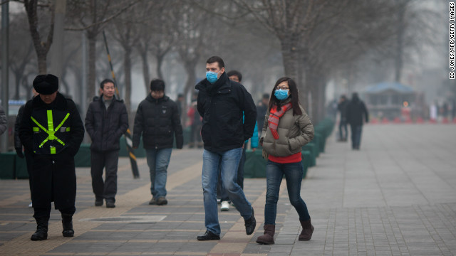 A couple wearing face masks walks in a busy shopping area during polluted weather in Beijing on January 13, 2013.