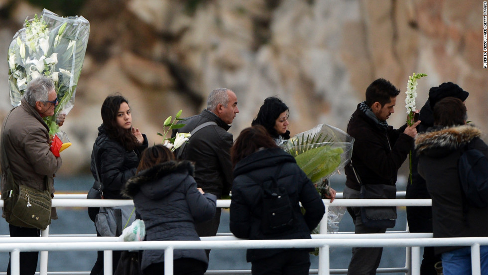 Relatives hold bouquets of flowers before throwing them into the sea on Sunday during commemorations.