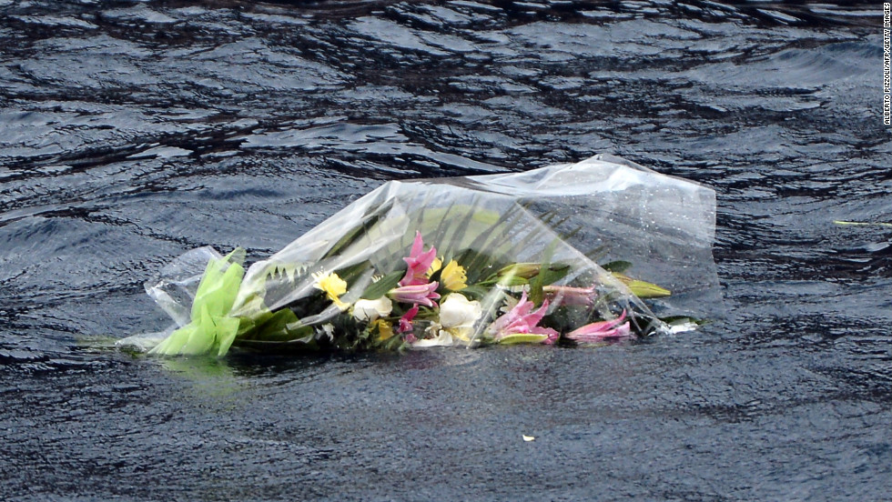 Flowers thrown into the sea by relatives Sunday float by the ship.