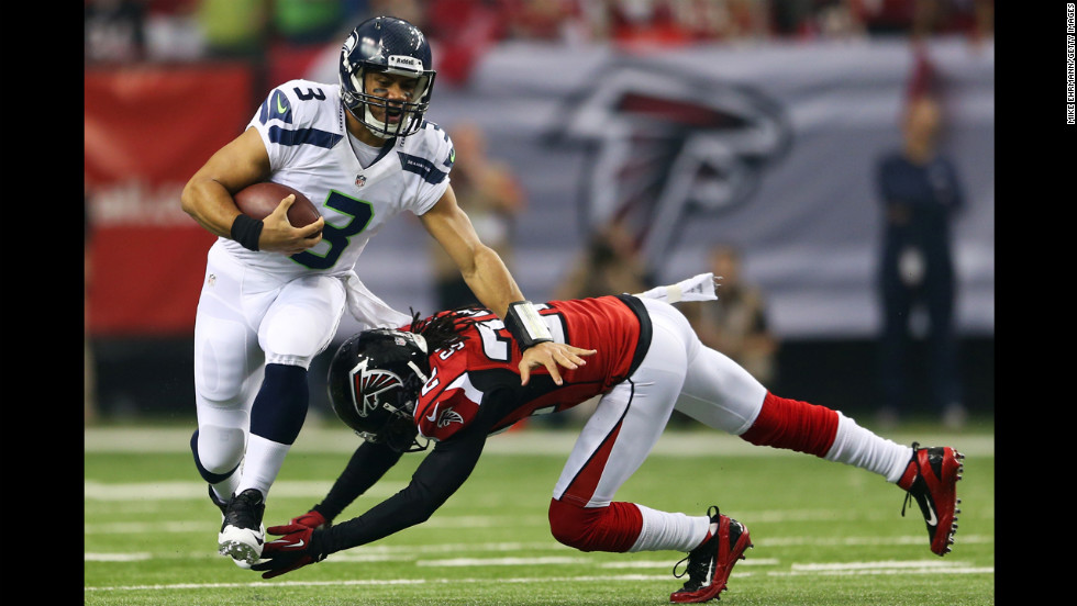 Quarterback Russell Wilson of the Seahawks tries to avoid the Falcons' Jacquizz Rodgers in the first quarter Sunday.