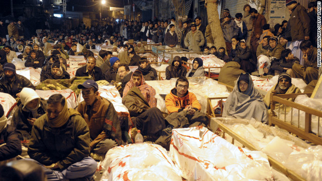 Pakistani Shiite Muslims demonstrate and sit between the coffins of bomb blast victims in Quetta on January 12, 2013.