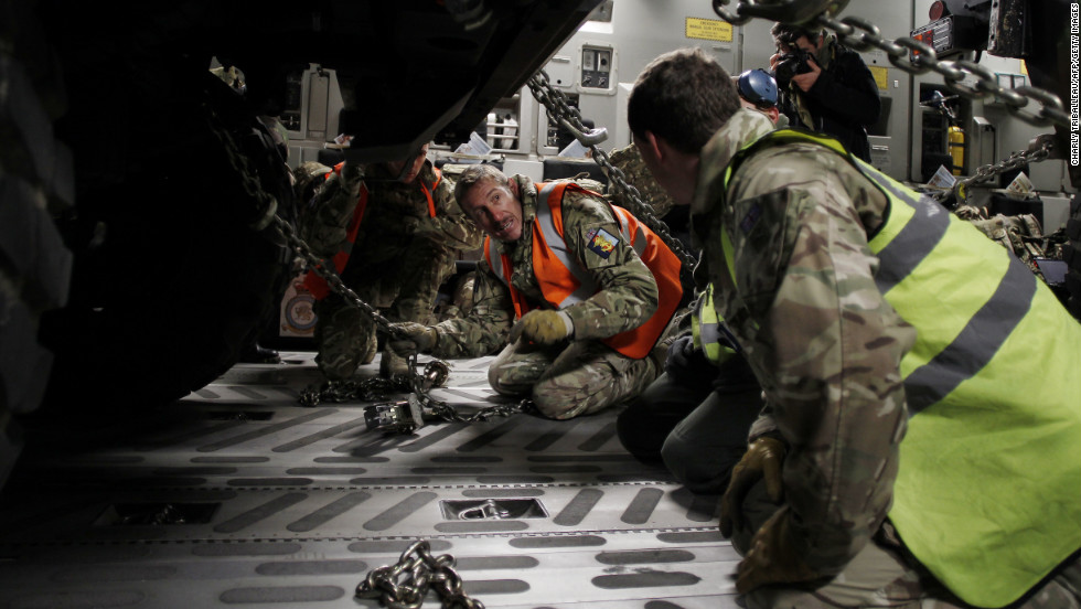 Workers adjust chains on a vehicle load in the C-17 in Evreux on Sunday.