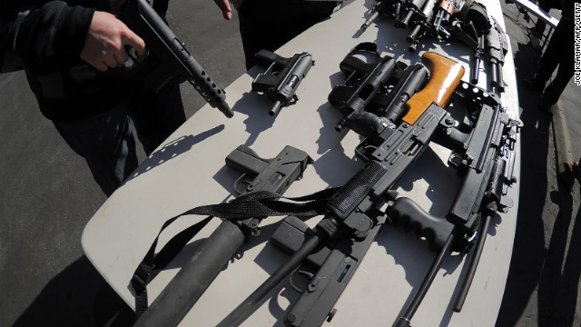 A police officer oversees assault weapons collected at the LAPD's gun buyback event on December 26, 2012.