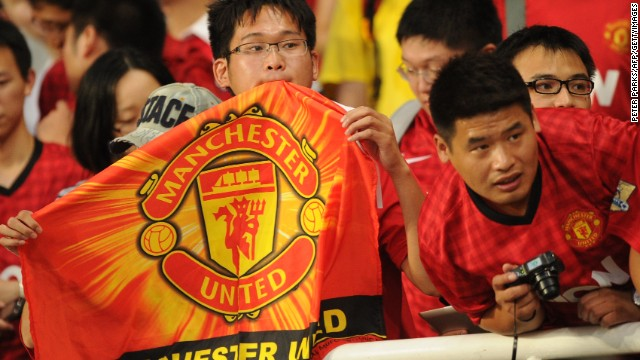 Manchester United fans look on as the team arrives for a team training session at Shanghai Stadium in Shanghai on July 24, 2012.