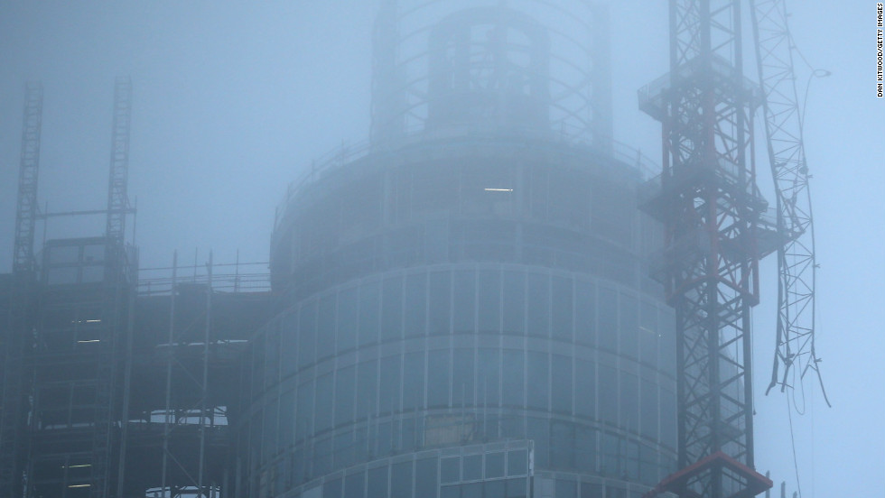 Fog surrounds a damaged crane attached to St Georges Wharf Tower after a helicopter reportedly collided with it.