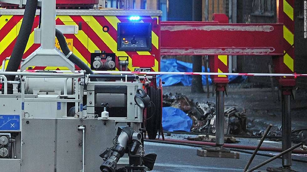 Debris is pictured beside a fire fighting vehicle at the scene of a helicopter crash.