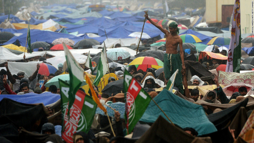 A supporter of Tahir-ul Qadri enjoys the rain at a protest rally in Islamabad on January 17.