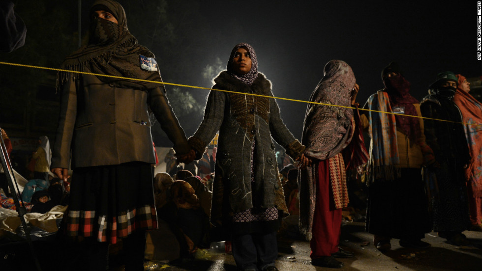 Tahir-ul Qadri's female supporters stand guard to protect sleeping women taking part in the fourth day of protests in Islamabad early on January 17.