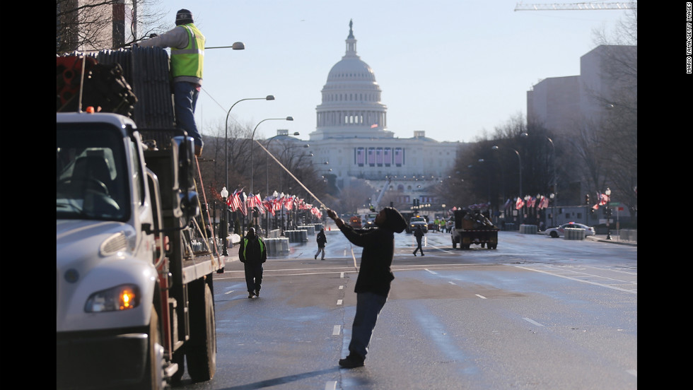 Workers prepare the parade route in front of the U.S. Capitol building on Sunday.