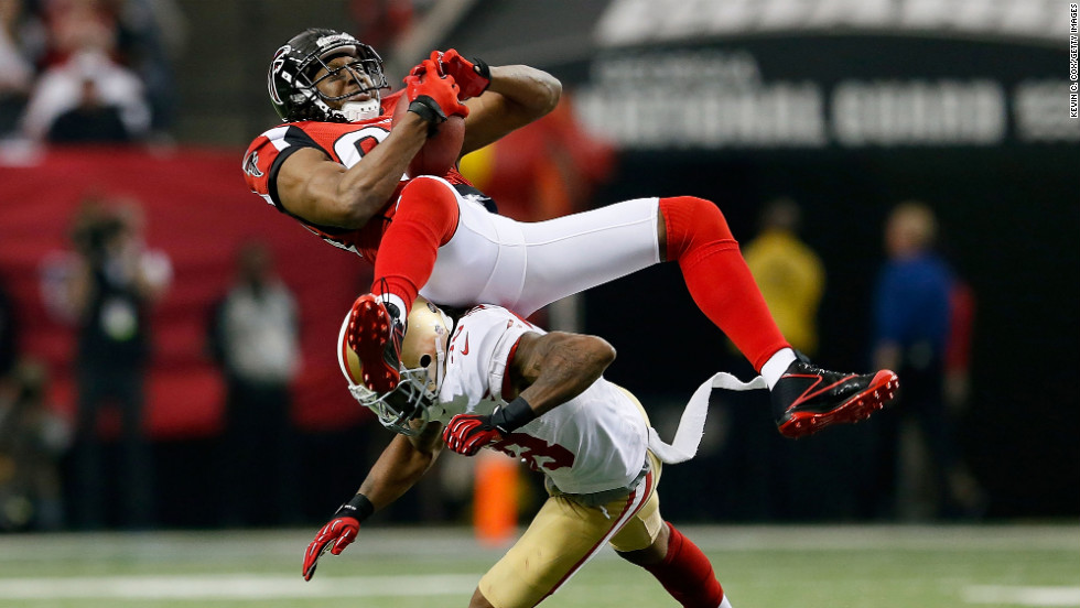Roddy White of the Atlanta Falcons catches a pass as he is hit by Dashon Goldson of the San Francisco 49ers.