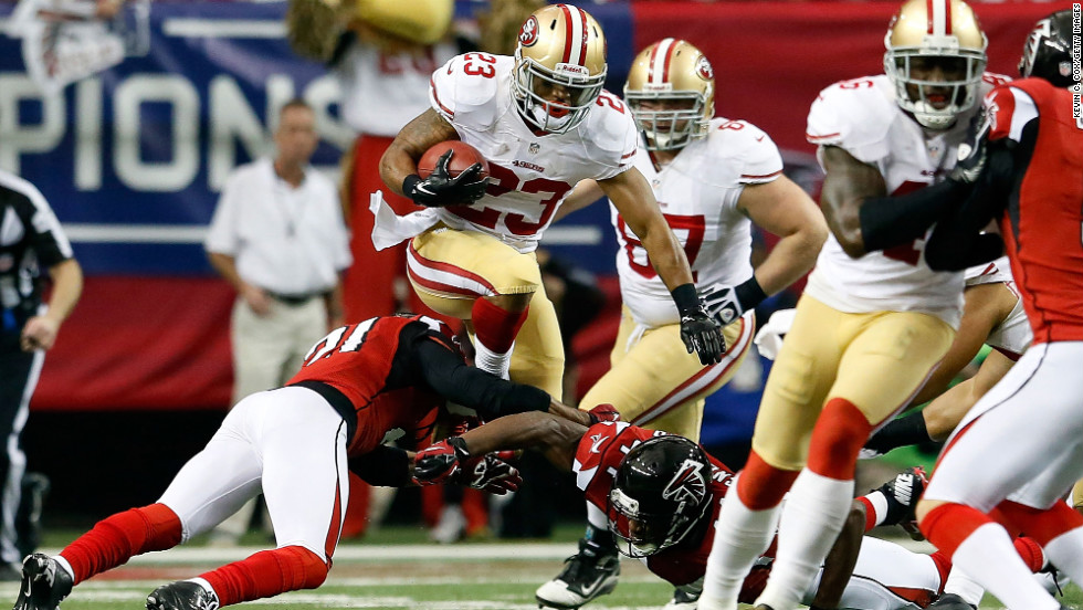 LaMichael James of the San Francisco 49ers leaps over Falcons defenders during a kick return in the first half.
