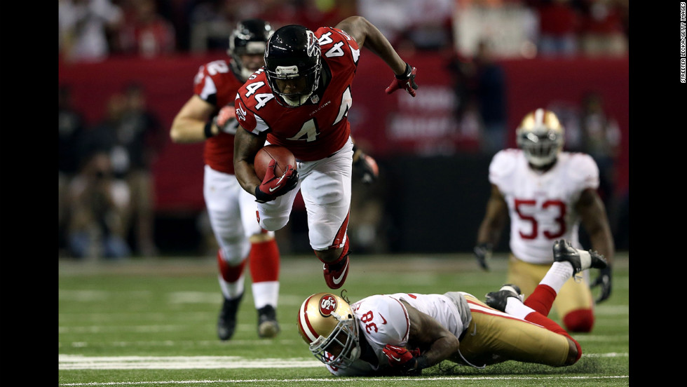 Jason Snelling of the Atlanta Falcons flies in the air over Dashon Goldson of the San Francisco 49ers.