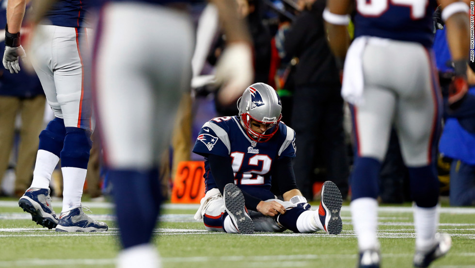 Tom Brady of the Patriots sits on the ground after getting knocked down in the game against the Ravens.
